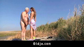 Charming busty teenager in white bikini fucks an aged man in the field
