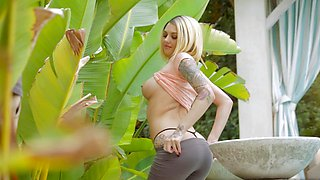 A blonde with tattoos on her body is undressing outside