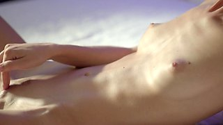 Blonde with small tits is on the bed, massaging her meaty pussy