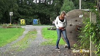 Blond haired pregnant chick sits behind the wooden barrel and pisses