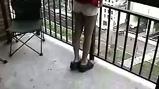 This whore has always loved masturbating on her balcony and she's so kinky