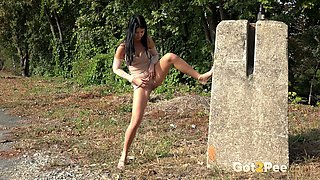 Slender and wild flexible brunette stands near the country road and pees